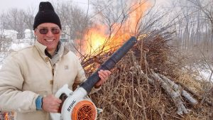 Author with leaf blower brush pile burning in the background.