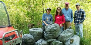 Image of volunteers posing with bags of garlic mustard